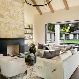 Immagine di un soggiorno moderno aperto con sala formale, pavimento in cemento, camino classico, cornice del camino in pietra, nessuna TV e pavimento beige