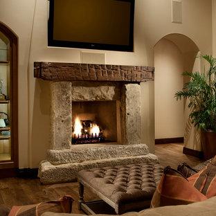 フェニックスの大きい地中海スタイルのおしゃれなLDK (壁掛け型テレビ、ベージュの壁、標準型暖炉、石材の暖炉まわり、濃色無垢フローリング) の写真