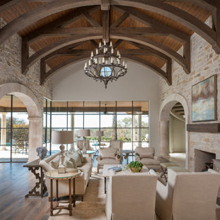 Expansive mediterranean open plan living room in Dallas with medium hardwood flooring, a standard fireplace, a stone fireplace surround and brown floors.