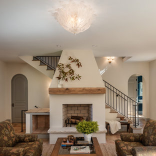 Large mediterranean open plan living room in Other with beige walls, terracotta flooring, a standard fireplace, a plastered fireplace surround, no tv and pink floors.