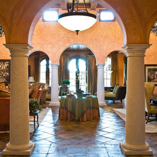 Example of a huge tuscan living room design in Miami with orange walls