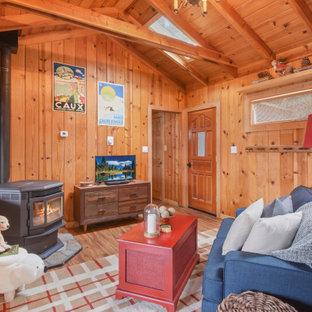 Rustikales Wohnzimmer mit brauner Wandfarbe, braunem Holzboden, Kaminofen, braunem Boden, Holzdecke und Holzwänden in Sacramento