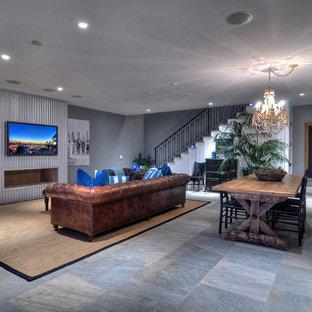オレンジカウンティの広いビーチスタイルのおしゃれなLDK (グレーの壁、スレートの床、金属の暖炉まわり、フォーマル、横長型暖炉、壁掛け型テレビ) の写真