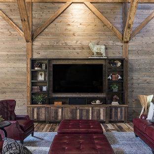 Diseño de salón campestre con paredes marrones, suelo de madera en tonos medios, pared multimedia y suelo marrón
