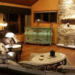 デンバーの中サイズのヴィクトリアン調のおしゃれなLDK (フォーマル、内蔵型テレビ、オレンジの壁、無垢フローリング、標準型暖炉、石材の暖炉まわり) の写真