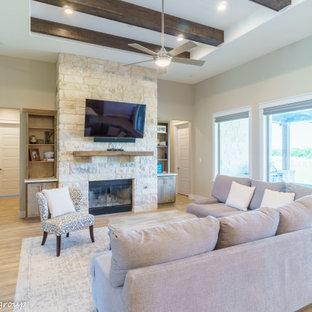 オースティンの中くらいのラスティックスタイルのおしゃれなLDK (ベージュの壁、淡色無垢フローリング、標準型暖炉、石材の暖炉まわり、壁掛け型テレビ、ベージュの床、折り上げ天井) の写真