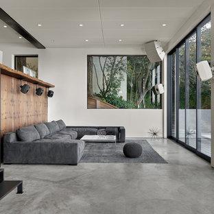 Ispirazione per un grande soggiorno moderno aperto con angolo bar, pareti bianche, pavimento in cemento e pavimento grigio