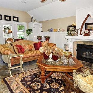 ミルウォーキーの小さいビーチスタイルのおしゃれなLDK (ベージュの壁、ライムストーンの床、標準型暖炉、木材の暖炉まわり、据え置き型テレビ) の写真