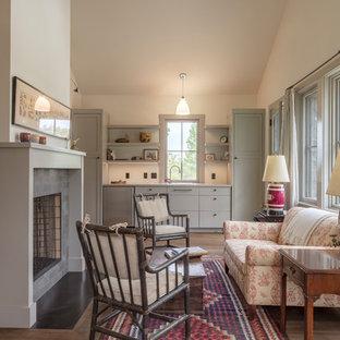 Lantlig inredning av ett vardagsrum, med ett finrum, vita väggar, mellanmörkt trägolv, en standard öppen spis och en spiselkrans i sten