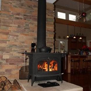 グランドラピッズのトラディショナルスタイルのおしゃれなLDK (ベージュの壁、無垢フローリング、薪ストーブ、石材の暖炉まわり) の写真