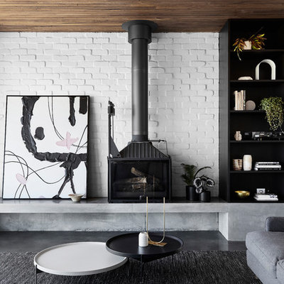 Living room - large contemporary open concept concrete floor and gray floor living room idea in Melbourne with white walls and a wood stove