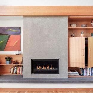 Imagen de salón abierto, contemporáneo, con paredes blancas, suelo de madera clara, chimenea tradicional, televisor retractable y suelo beige