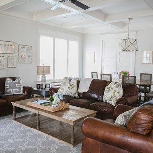 Стильный дизайн: открытая гостиная комната в классическом стиле с темным паркетным полом, телевизором на стене и серыми стенами - последний тренд