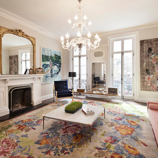 This is an example of a traditional formal enclosed living room in New York with a standard fireplace, a plastered fireplace surround, a concealed tv, beige walls, dark hardwood flooring and brown floors.