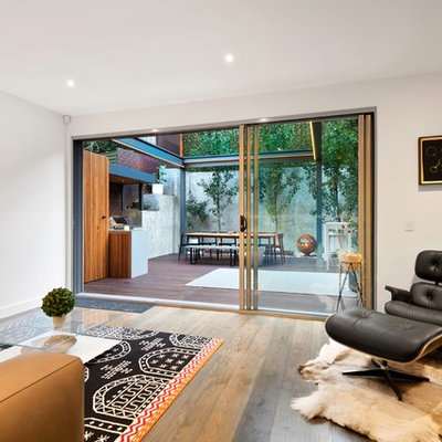 Example of a mid-sized trendy formal medium tone wood floor and brown floor living room design in Melbourne with white walls and a wall-mounted tv