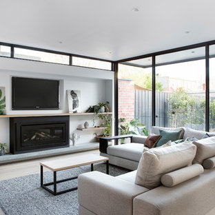 Photo of a modern open concept living room in Melbourne with white walls, light hardwood floors, a ribbon fireplace, a wall-mounted tv and beige floor.