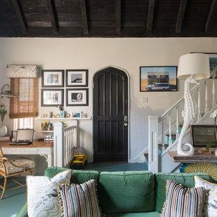 Réalisation d'un salon bohème ouvert avec un mur blanc, un sol en bois peint et un sol turquoise.
