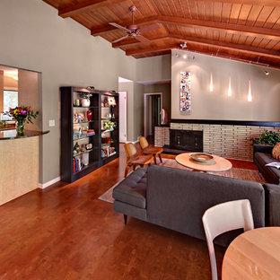 Cette photo montre un salon rétro de taille moyenne et ouvert avec un mur gris, un sol en liège, un manteau de cheminée en brique et aucun téléviseur.