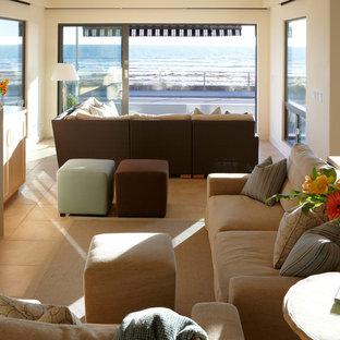 サンフランシスコの中サイズのビーチスタイルのおしゃれなLDK (ベージュの壁、トラバーチンの床、標準型暖炉、タイルの暖炉まわり、壁掛け型テレビ、ベージュの床) の写真