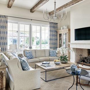 Неиссякаемый источник вдохновения для домашнего уюта: большая открытая гостиная комната в средиземноморском стиле с бежевыми стенами, паркетным полом среднего тона, стандартным камином, фасадом камина из штукатурки, телевизором на стене и бежевым полом