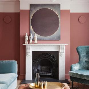 Foto de salón cerrado, actual, pequeño, con paredes rosas, suelo de madera clara, chimenea tradicional y suelo beige