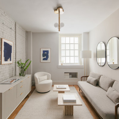 Living room - small contemporary formal and enclosed medium tone wood floor, brown floor and brick wall living room idea in New York with white walls, no fireplace and no tv