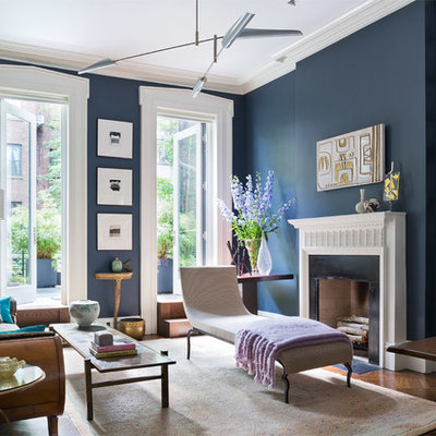 Large transitional open concept medium tone wood floor living room library photo in New York with blue walls, a standard fireplace and no tv