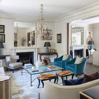 Example of a mid-sized transitional enclosed and formal light wood floor and gray floor living room design in London with white walls, a standard fireplace and no tv