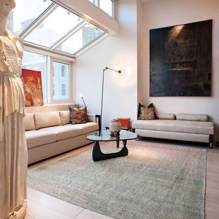 Example of an eclectic open concept light wood floor living room design in New York with white walls, no fireplace and no tv