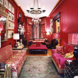 ニューヨークの中サイズのヴィクトリアン調のおしゃれな独立型リビング (フォーマル、赤い壁、無垢フローリング、標準型暖炉、テレビなし、茶色い床) の写真