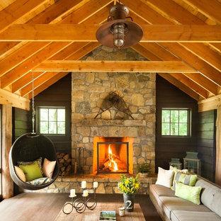 Réalisation d'un salon chalet avec une cheminée standard et un manteau de cheminée en pierre.