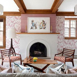Idee per un soggiorno classico con pareti rosa, pavimento in legno massello medio, camino classico, cornice del camino in mattoni, pavimento marrone, travi a vista e carta da parati