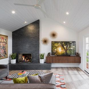 Idéer för ett 60 tals vardagsrum, med vita väggar, mellanmörkt trägolv, en standard öppen spis, en spiselkrans i sten, en fristående TV och brunt golv