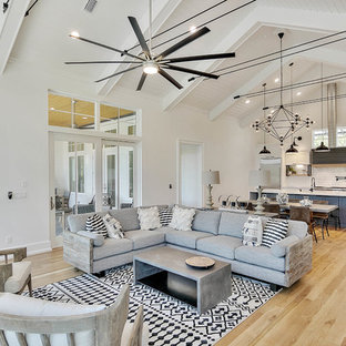 Example of a coastal open concept medium tone wood floor and brown floor living room design in Miami with white walls, no fireplace and no tv