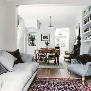 Farmhouse living room in London with white walls, medium hardwood flooring and brown floors.