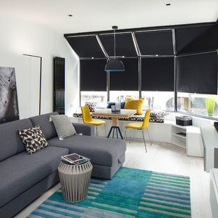 Medium sized contemporary open plan living room in Dublin with a reading nook, white walls, light hardwood flooring, a wall mounted tv and grey floors.