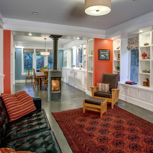 Inspiration for a mid-sized timeless open concept concrete floor living room remodel in Seattle with red walls, a wood stove and a media wall