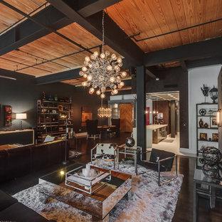 Inredning av ett industriellt stort allrum med öppen planlösning, med svarta väggar, målat trägolv, en väggmonterad TV och svart golv