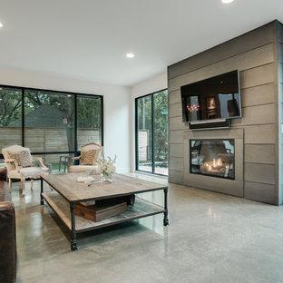 Idee per un grande soggiorno minimalista aperto con pareti grigie, pavimento in cemento e cornice del camino in metallo
