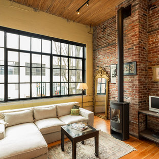 Ejemplo de salón abierto, industrial, de tamaño medio, con paredes amarillas, suelo de madera en tonos medios, estufa de leña y televisor independiente