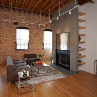 シカゴのインダストリアルスタイルのおしゃれなリビング (フォーマル、グレーの壁、竹フローリング、標準型暖炉、金属の暖炉まわり) の写真