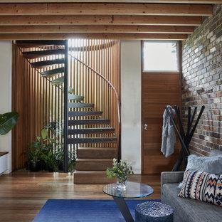 Industriell inredning av ett mellanstort allrum med öppen planlösning, med mellanmörkt trägolv, brunt golv och vita väggar