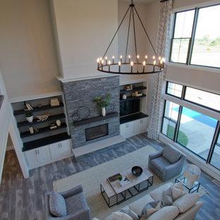 Imagen de salón para visitas abierto y abovedado, grande, con paredes beige, suelo vinílico, chimenea tradicional, televisor en una esquina y suelo gris