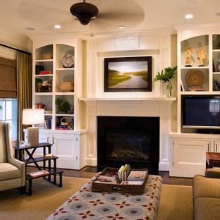 На фото: открытая гостиная комната среднего размера в классическом стиле с камином, мультимедийным центром, белыми стенами, темным паркетным полом, фасадом камина из камня и коричневым полом с