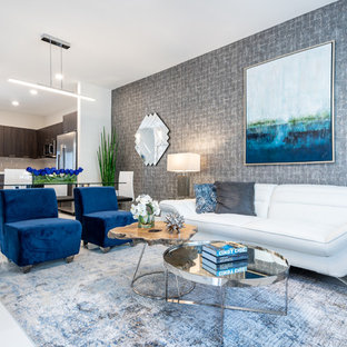 Modelo de salón abierto, moderno, de tamaño medio, con paredes grises, suelo de baldosas de porcelana, televisor colgado en la pared y suelo blanco