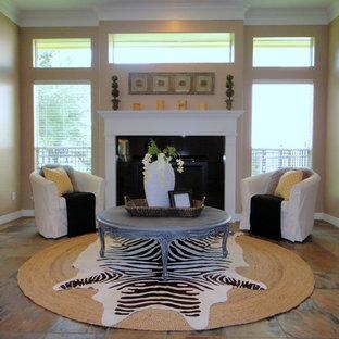 Immagine di un piccolo soggiorno eclettico aperto con sala formale, pavimento in ardesia, camino classico, cornice del camino in pietra, nessuna TV e pareti beige