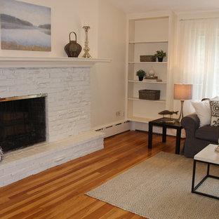 ボストンの広いビーチスタイルのおしゃれなLDK (黄色い壁、淡色無垢フローリング、標準型暖炉、レンガの暖炉まわり、テレビなし) の写真