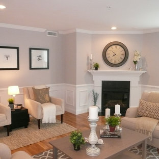 Large traditional open concept living room in Boston with grey walls, light hardwood floors, a corner fireplace, a wood fireplace surround and no tv.