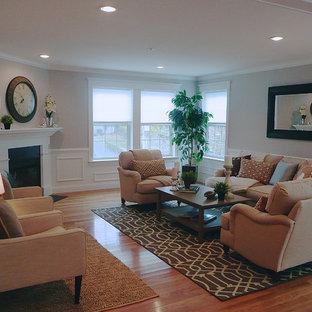 Foto de salón abierto, clásico, grande, sin televisor, con paredes grises, suelo de madera clara y chimenea de esquina