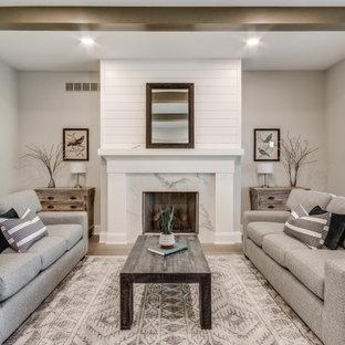 Foto di un soggiorno tradizionale chiuso con sala formale, pareti beige, pavimento in legno massello medio, camino classico, cornice del camino in pietra, nessuna TV e pavimento marrone